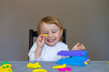 Cute little boy molds from colored plasticine on table. Home schooling. Creative leisure with children during virus quarantine staying at home.