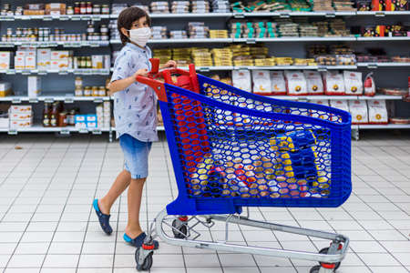 Brussels, Belgium - July 31, 2020: a young boy holding shopping grocery cart with food in a hypermarker Cora Woluwe. Child wearing protection mask during outbreak. Editorial