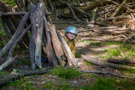 A young boy is playing in the forest in summer or spring. Toddler is building a wooden hut of logs and branches. Child hiding in wigwam created in the park. Archivio Fotografico
