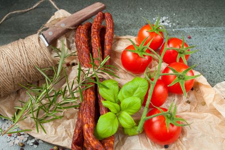 cherry tomatoes and dried sausages on a stone table