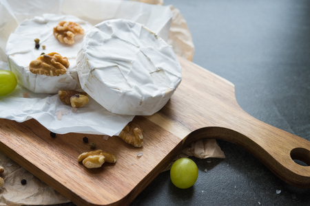 camembert cheese on a wooden board, decoration with nuts and grapes Banco de Imagens