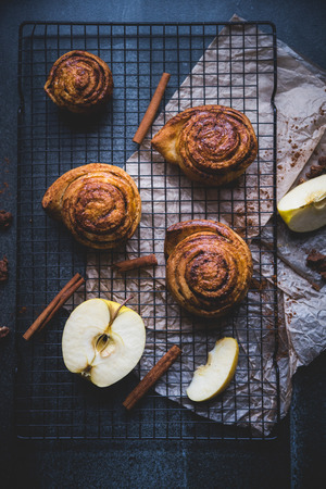 cinnamon rolls on the stone table, decoration with apples and cinnamon