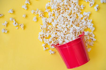 popcorn in a red bucket on a yellow background