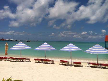 Beach umbrellas lined up on the beach on the island of St. Maarten.  Imagens