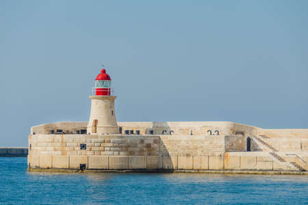 rungs: The lighthouse with red top of tower.There are visible rungs of the ladder to the lighthouse, the door to the lighthouse tower, the base of the lighthouse of yellow stone with embrasures. The lighthouse is located  of the blue sky and sea.