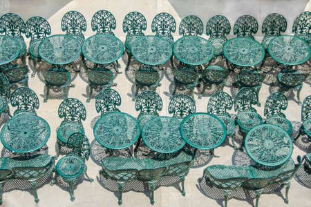 stay in the green: wrought iron tables and chairs, green in summer cafe or restaurant, stay  in two lines. It looks like an old French furniture in the cafe
