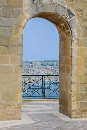 passageway: Through stone arched passageway seeing waterfront with many buildings and yachts