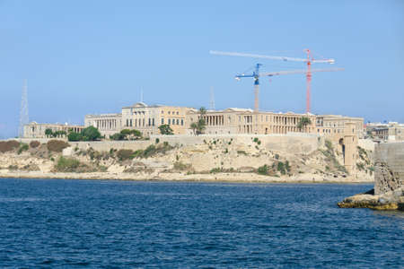 monumental: Monumental buildings and modern cranes on sky background, on the beach
