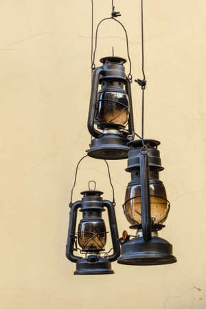 kerosene: Three kerosene lamps hanging on a light background walls Stock Photo