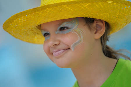 painted face: A little girl in a bright yellow hat and with painted face Stock Photo