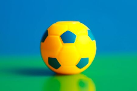 Small colorfull toy ball for football on a green and blue background