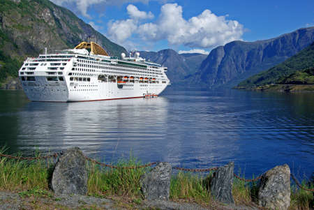 Mountainous landscape with a cruising ship in the fjord  photo