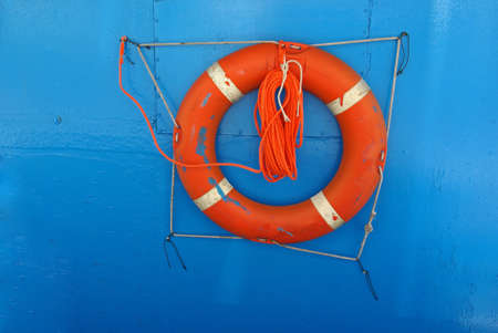 Orange lifebuoy on blue vessel wall for safety on board. photo