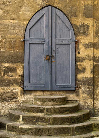 Blue wooden door and doorsteps to a medieval stone church. photo