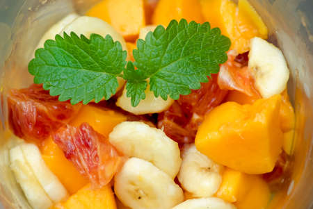 Bowl of fresh fruit salad and lemon balm leaves. photo