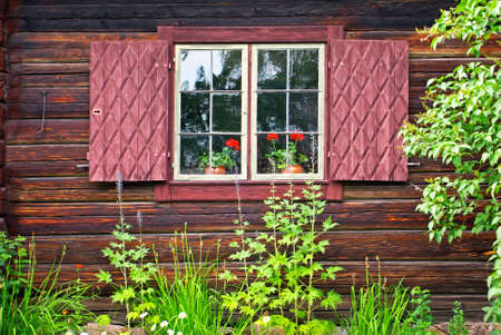 sweden: Window with window shutters on an old Swedish log cabin.