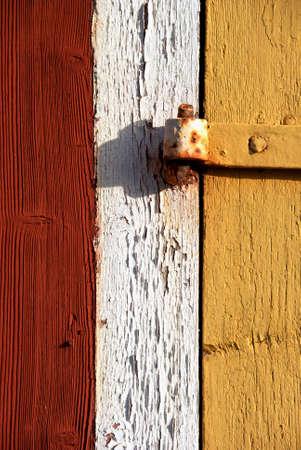 Rusty hinge on yellow old wooden barn door. photo