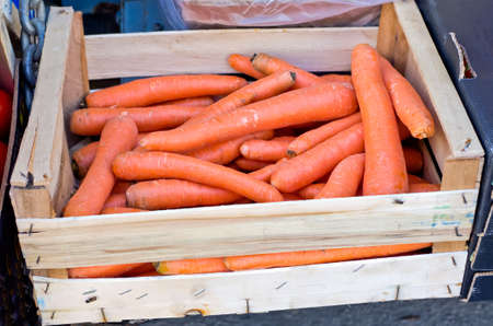 Carrots in wooden box for sale at farmers market. photo