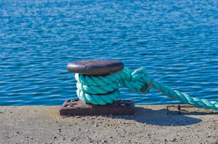 anchoring: Anchoring on a bollard with a blue hawser. Stock Photo