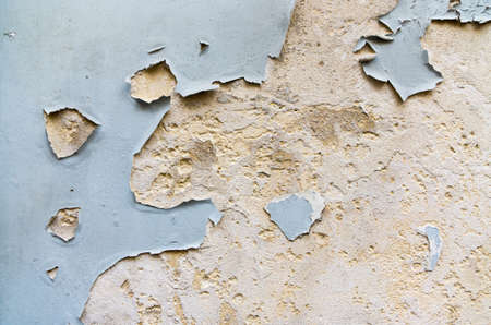 flaking: House wall of stone with painting in flakes.