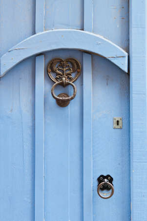 Blue door with black door knocker and handle in wrought iron. photo