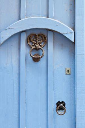 Blue door with black door knocker and handle in wrought iron. photo