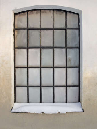 Window with frosty panes and snow on the windowledge  photo