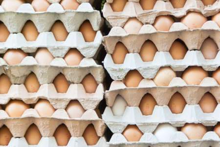 Stack with fresh hens eggs in egg cartons for sale at farmers market  photo