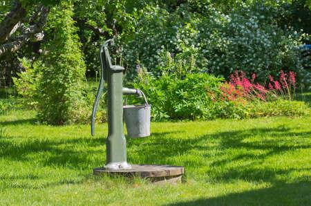bomba de agua: Jard�n con una bomba de agua y su cubo de zinc