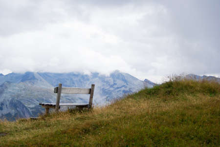 Wooden bench for resting in a mountainous landscape a cloudy day in Austria. photo