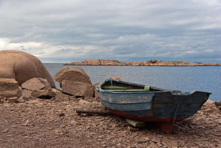 old boat: Landscape with ocean and red granite boulders and an old rowing boat at the Swedish west coast. Stock Photo