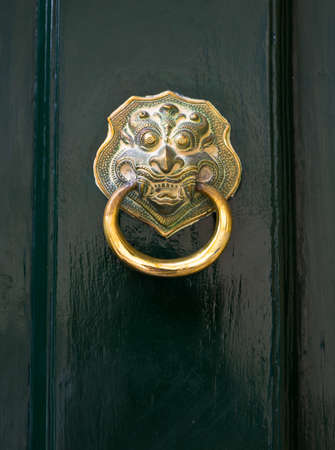 lionhead: Green front door with golden lion head as door knocker.