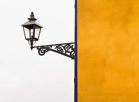 outdoor lighting: Yellow building with outdoor lighting in the old style against a gray sky. Stock Photo