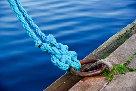 Two blue rope with many knots around a mooring ring in a harbor. Stock Photo