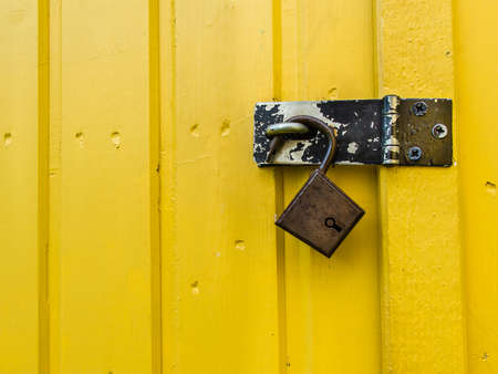 Old rusty padlock hanging on yellow wooden wall. photo