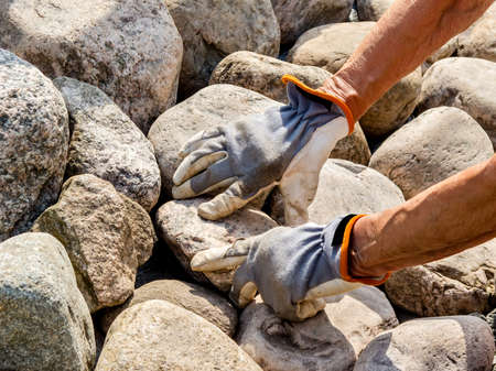 Hands with work gloves adds a stone in a stone setting. Stock Photo - 18394511