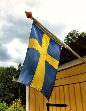 the swedish flag: Swedish flag on yellow wooden building  Stock Photo