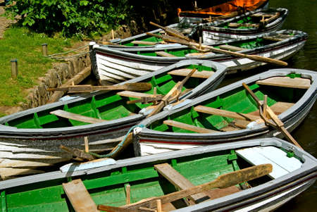 waters  edge: Lots of rowing boats for hire lies at the waters edge  Stock Photo