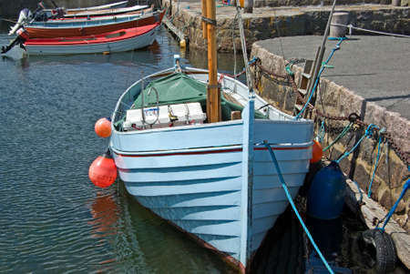 Blue fishing boat moored at a quay in a harbor  photo