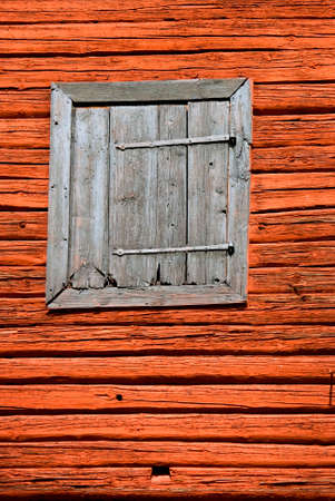 timbered: Red painted timbered barn with a gray shutter  Stock Photo