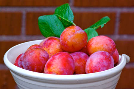 stoneware: Fresh plums with its green leaf in stoneware bowl  Stock Photo