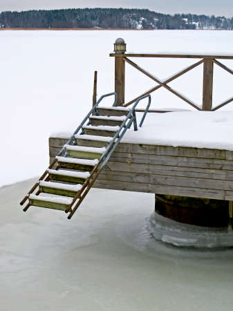 Bridge with ladder in winter with frozen sea  photo