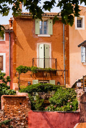 Orange stone buildings with lush garden in France  photo