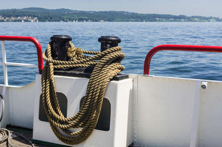 Boat with mooring rope around a bollard on board. photo