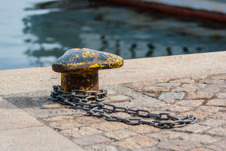 Stone paved quay with berth and chain on the ground. Stock Photo