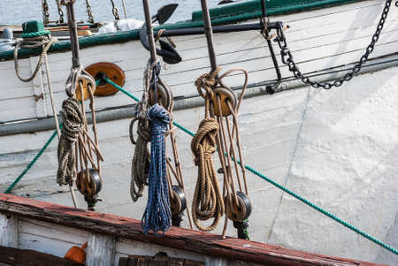 pulleys: Part of sailing ship with pulleys and knotted ropes.