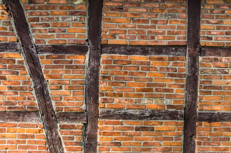 wooden beams: Half-timbered wall with red brick and brown wooden beams in Germany.