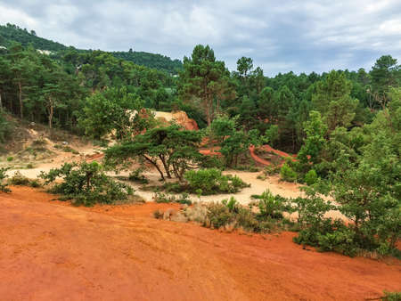 Nature reserve called Colorado Provencal in France with trees and orange colored sand dunes high as mountaines a rainy day in summer. Stock Photo