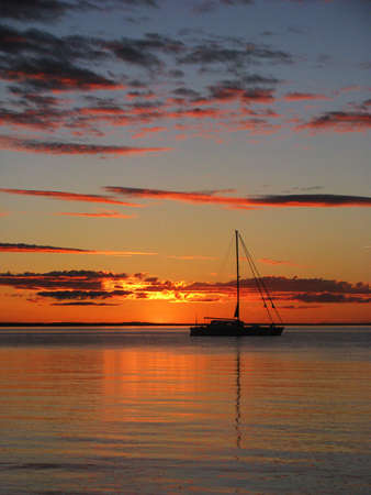 fraser: Sunset at Fraser Island with boat on the ocean Stock Photo