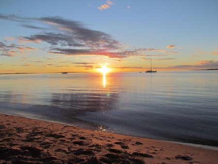 Australia Sunset at Fraser Island with boat on the ocean Standard-Bild